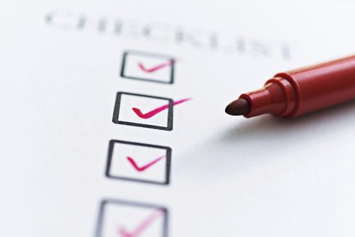 Checklist with checkboxes ticked by red felt tip pen.